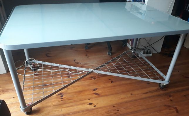 Stół z IKEA na kółkach: srebrna rama z mlecznym, hartowanym szkłem.