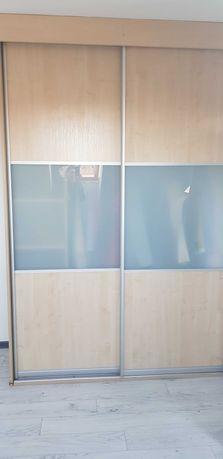 Szafa do zabudowy z drzwiami przesuwnymi w ramie aluminiowej.