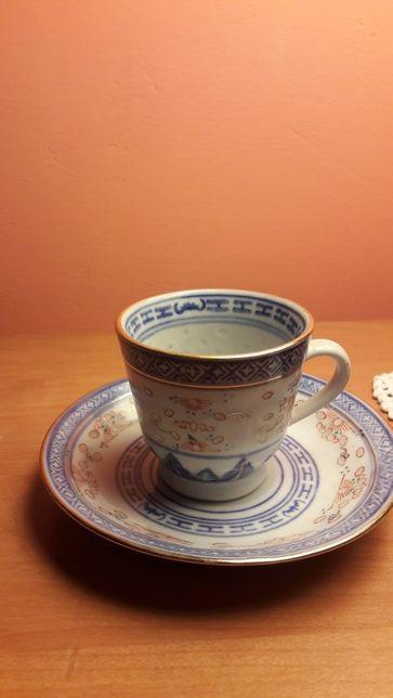 Dwie filiżanki z chińskiej ryżowej porcelany z talerzykami.