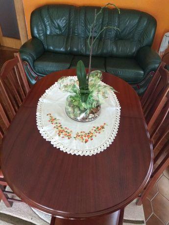 Mesa de jantar com seis cadeiras e um sofá em pele