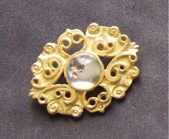 Pregadeira dourada com pedra no centro