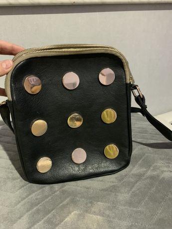 Czarna torebka listonoszka ze złotymi kółkami