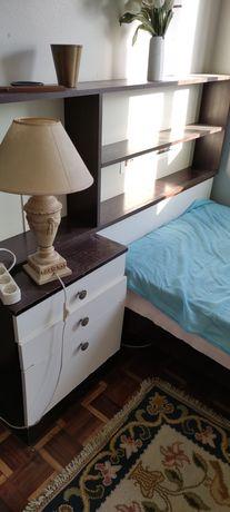 Cama solteiro com estante e mesa cabeceira.