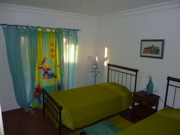 camas individuais em ferro e Madeira e mesa cabeceira