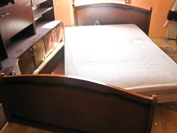 Duże drewniane łóżko z materacem, sypialnia