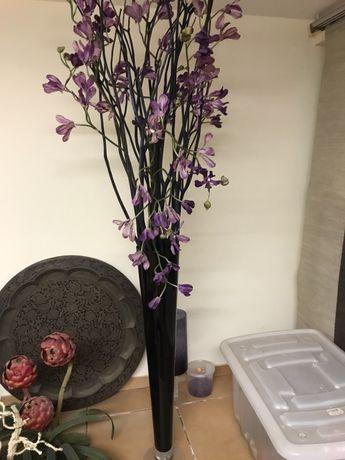 Peça em vidro preto com arranjo de orquídeas