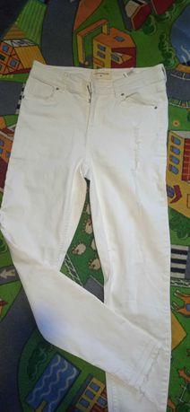 Reserved białe spodnie z przetarciami