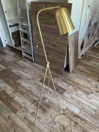 Złota lampa podłogowa na trójnogu