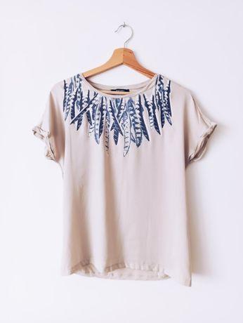 Beżowa bluzka z łączonych materiałów z nadrukiem piórka 38