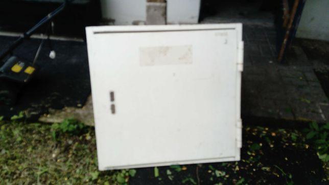 Drzwi metalowe kwadratowe z futryną, o długości boku około 84cm.