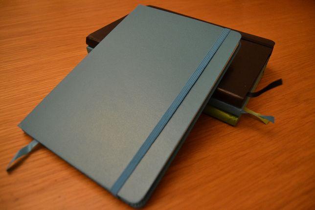 Blocos de notas azul, verde e negro
