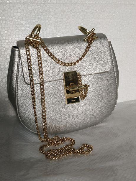 Продам небольшую, серебристую сумку с золотого цвета фурнитурой.