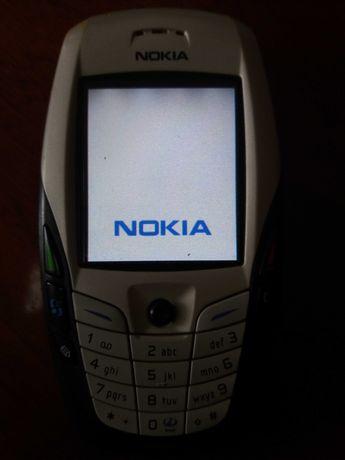 Telemóvel Nokia 6600 com câmara traseira a trabalhar com carregador