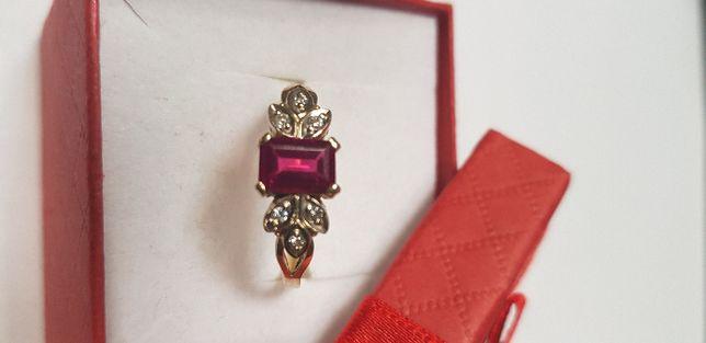Złoty pierścionek z cyrkoniami i czerwonym oczkiem.