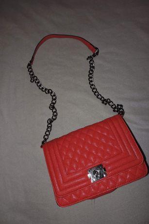 Czerwona torebka na łańcuszku.