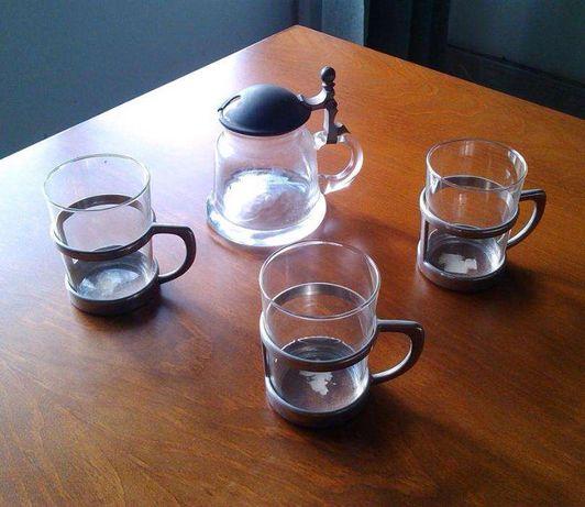 Três copos e um bule de vidro e estanho.