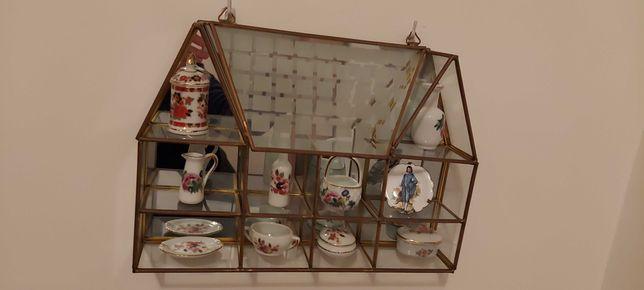 Peça decorativa em vidro com formato de casa e com bibelots miniatura