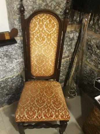 Cadeira de madeira escura, muito antiga, cor amarela alaranjada.