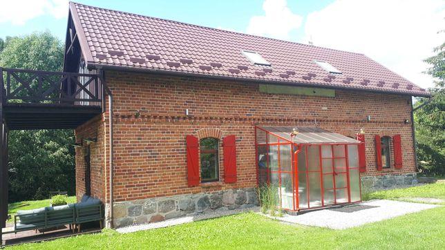 siedlisko na Mazurach z linią brzegową rzeczki dom z czerwonej cegły