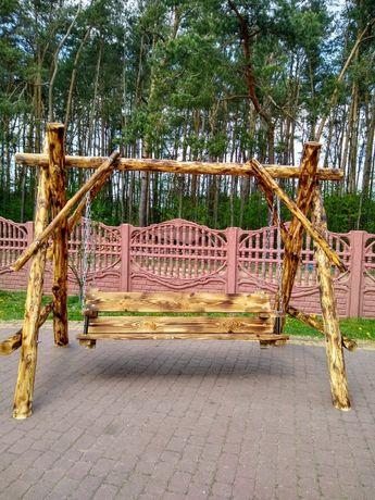 Huśtawka ogrodowa, drewniana z siedziskiem dla dziecka lub daszkiem.