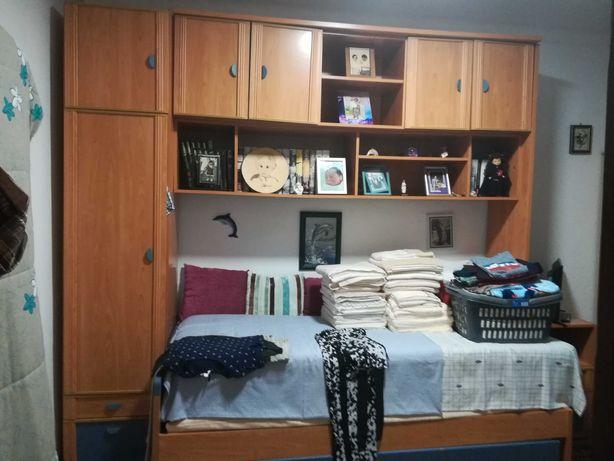 Estúdio com roupeiro, cama e mesinha de cabeceira