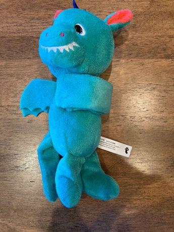 Pluszowy dinozaur trzymający szczebelki łóżeczka