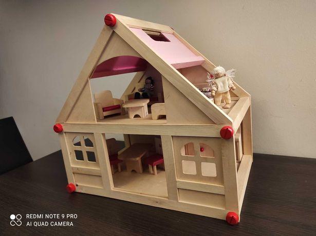 Drewniany domek dla lalek z mebelkami i małymi laleczkami.