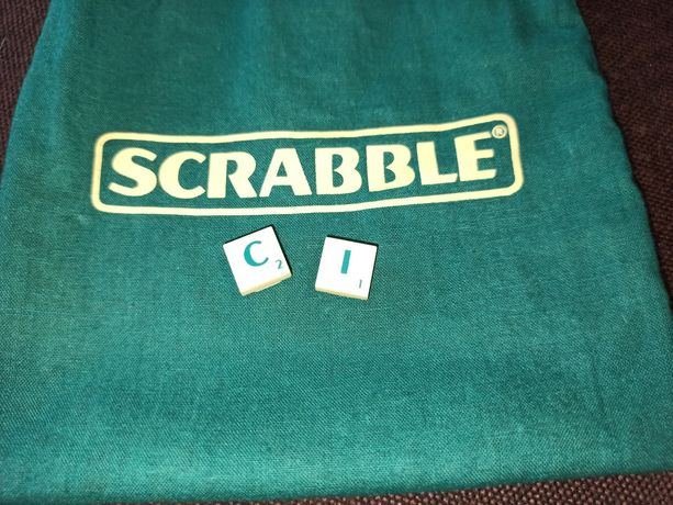 Oryginalny woreczek i dwie widoczne literki do Scrabble travel