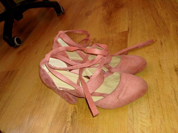 Różowe buty na słupku wiązane przy kostce