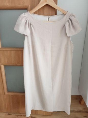 Sukienka w kolorze beżowym.