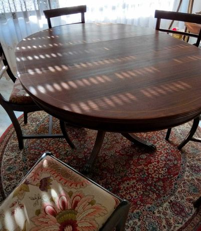 Mesa redonda extensível com 6 cadeiras estufadas.