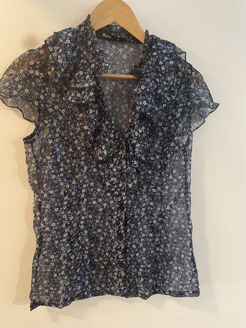 Delikatna zwiewna bluzka z krótkim rękawem niebieska w kwiaty. Guziki