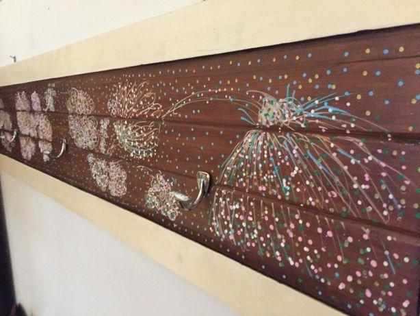 Cabide em madeira em tons de beije e motivos florais pintados.