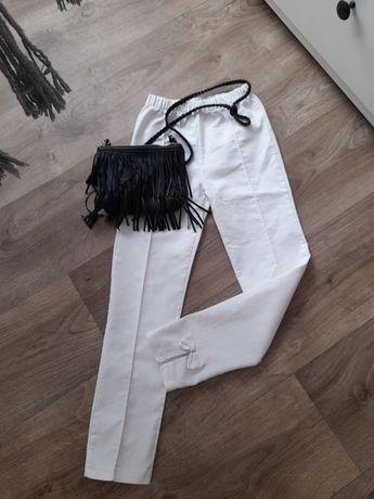 Spodnie białe eleganckie z kokardkami 128/134