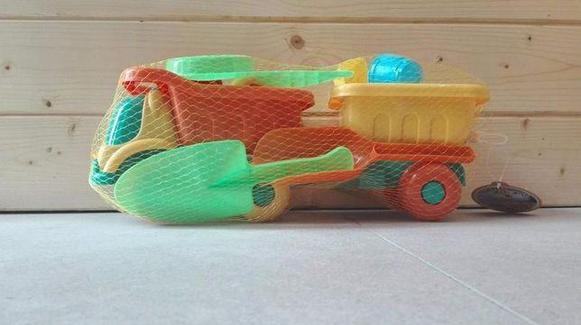 Samochodzik z przyczepką i narzędziami do piasku.