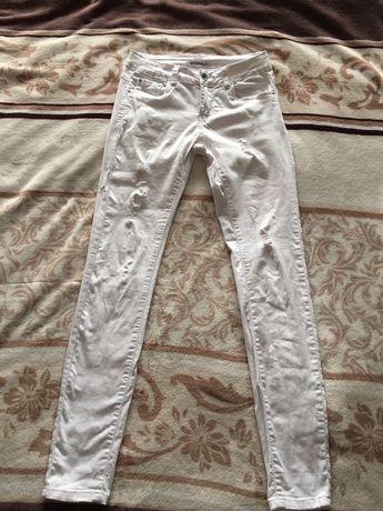 Biale spodnie rurki z przetarciami i dziurami