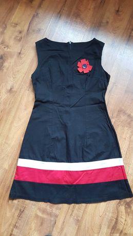 Czarna sukienka z ozdobnym kwiatkiem.