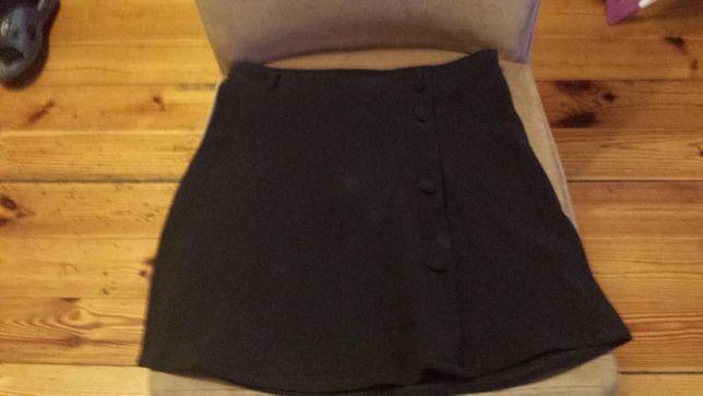 Czarna spódniczka z guzikami lekko rozkloszowana.