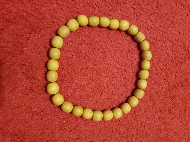 Żółte, drewniane korale na gumce