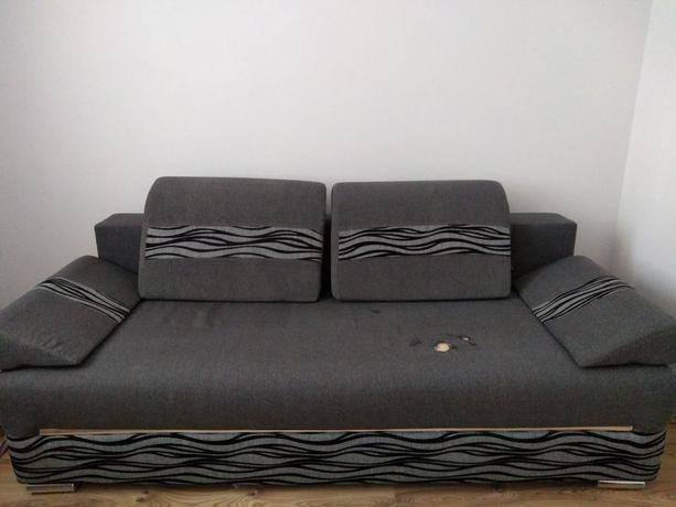 Szara kanapa rozkładana.