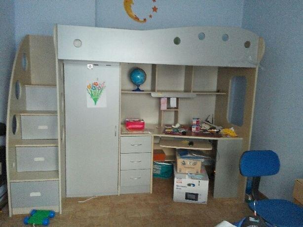 Łózko piętrowe z szafą i biurkiem.
