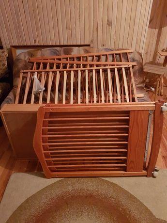 Używane łóżeczko drewniane na kółkach dla niemowlaka.