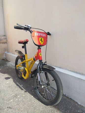 Детский велосипед с дополнительными маленькими колесами.