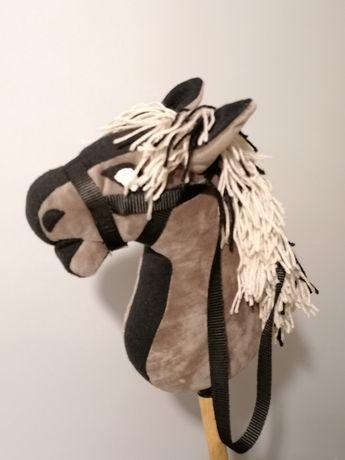 Hobby horse mały z ogłowiem i wodzami osadzony na kiju.