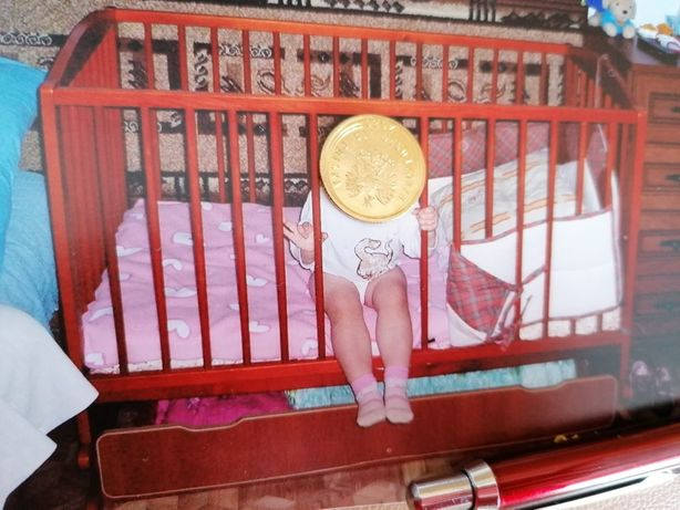 Łóżeczko dziecięce z funkcją bujania i szufladą.