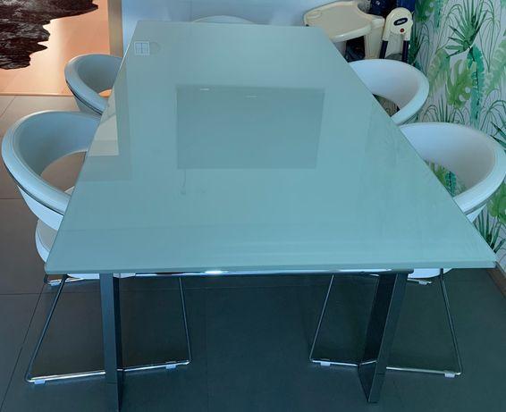 Mesa com tampo branco em vidro e estrutura em inox extensível