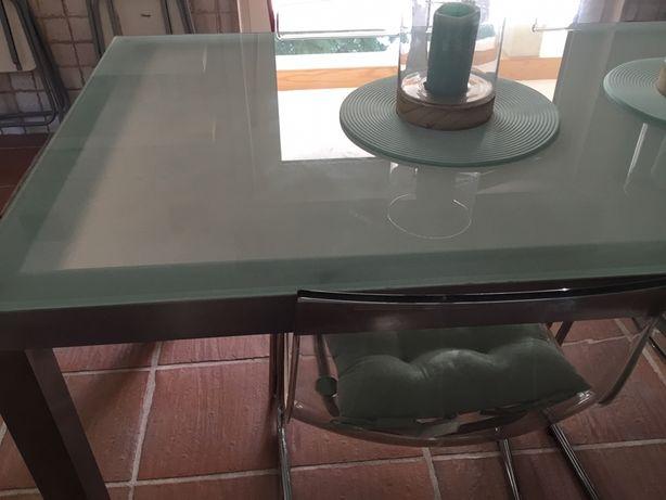 Mesa com estrutura em inox e tampo de vidro e 4 cadeiras em acrilico