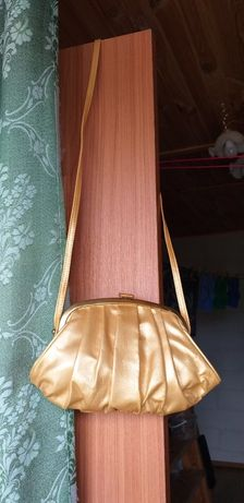 Сумочка на плече золотая.