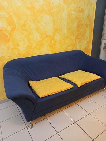 Sofa granatowa z dwoma żółtymi poduszkami