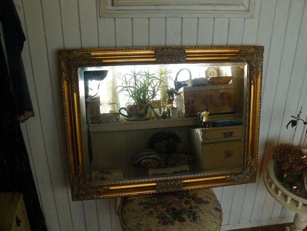 Fazowane lustro w ozdobnej złoconej ramie .